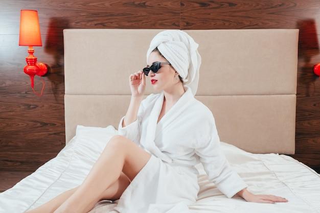 美容ケア。スパの贅沢。ベッドでポーズをとるバスローブを着た若い女性。サングラスとタオルターバン。女性のリラックスタイム。