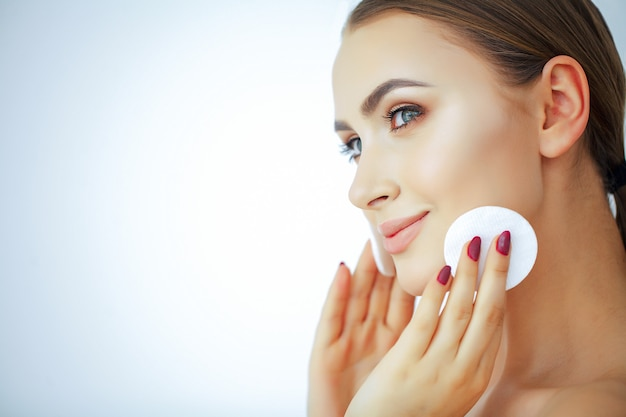 Beauty and care. young beautiful woman with pure skin. holds in hand cotton pads. portrait of a woman with a smile.