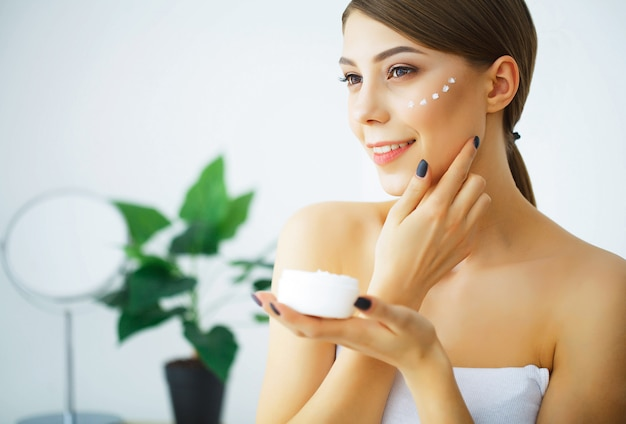 Beauty and care. young woman with cream for face in hands. morni