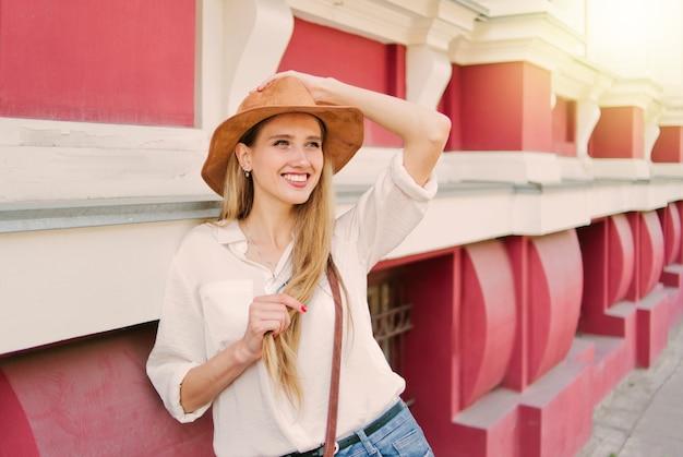 오래 된 도시 건축의 배경에 대해 포즈 펠트 모자에 아름다움 캐주얼 스타일 여자