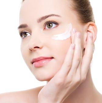 目の下に化粧品を適用する美容白人若い女性