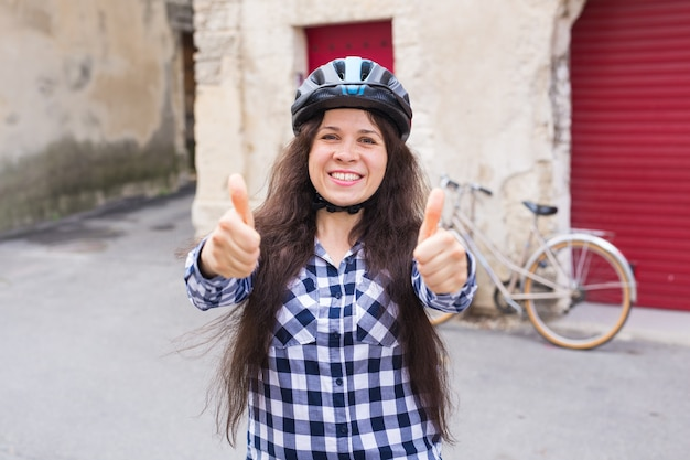 自転車と赤いドアに親指をあきらめる美しさの陽気な女性