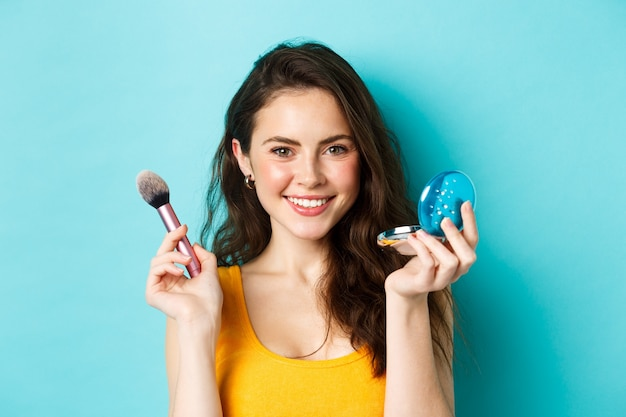 Beauty. close up of attractive stylish woman applying make up, holding brush and cute pocket mirror, smiling satisfied at camera, standing over blue background