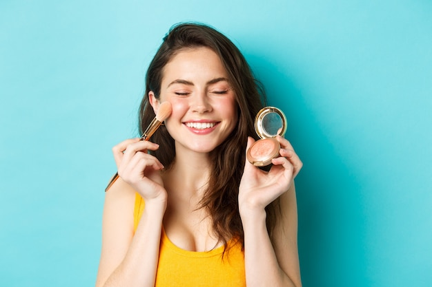 Beauty. close up of beautiful young woman close eyes and smile while applying blushes on cheeks with make up brush, standing happy against blue background