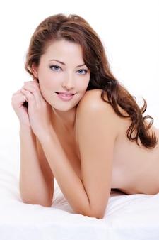 ベッドに横たわっている若い裸の女性の美しさのクローズアップ顔