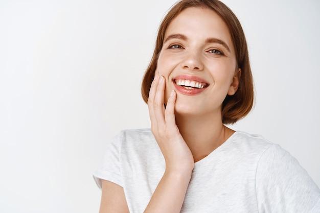 Bellezza. primo piano di una donna felice con i capelli corti, che tocca la pelle del viso fresca e pulita e sorride, che mostra denti e viso perfetti, in piedi contro il muro bianco