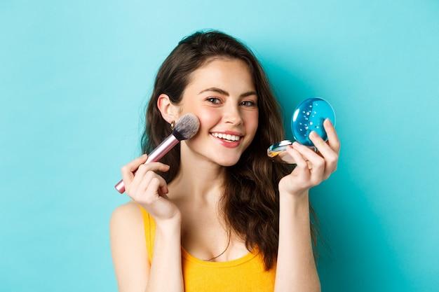 아름다움. 거울을 보고 브러시를 사용하여 화장을 하고, 카메라를 보고 기뻐하며 파란 배경에 서서 웃는 매력적인 여성의 클로즈업.