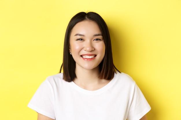 아름다움. 완벽 한 하얀 미소 이빨과 빛나는 피부, t- 셔츠에 노란색 배경 위에 서있는 웃는 귀여운 아시아 여자의 닫습니다.