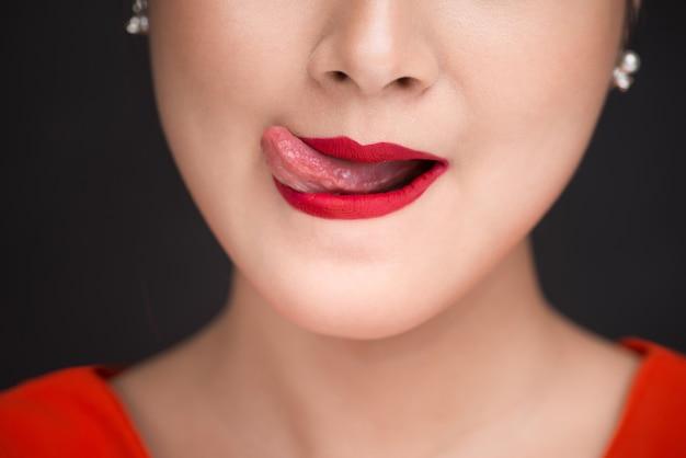Красота. крупным планом вид губ красивой женщины с красной матовой помадой, демонстрирующей ее желание