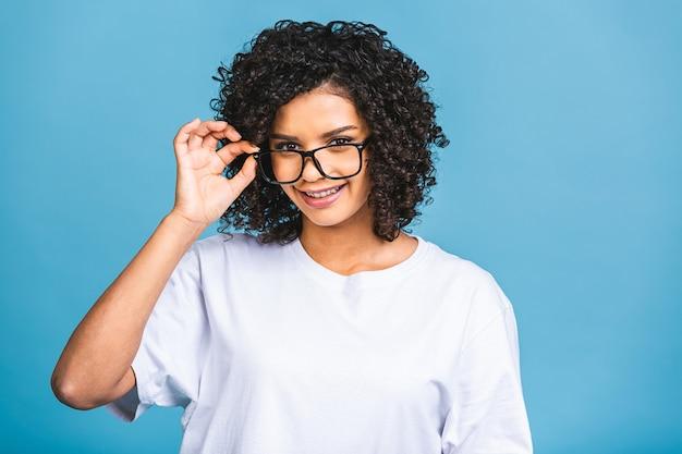 아프로 머리를 가진 젊은 아프리카 계 미국인 여자의 아름다움 근접 촬영 초상화. 카메라를보고하는 소녀. 파란색 배경 위에 격리.