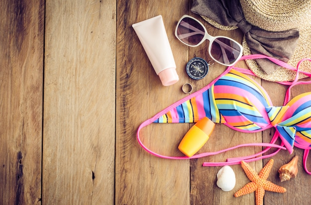 Beauty colorful bikini and accessories on wooden floor for trip on summer
