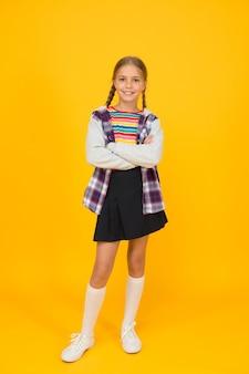 아름다움은 패션이 성공할 때 옵니다. 아늑한 패션의 어린 소녀는 노란색 배경을 착용합니다. 작은 패션 모델의 가을 모습. 아이들을 위한 추운 날씨 패션.