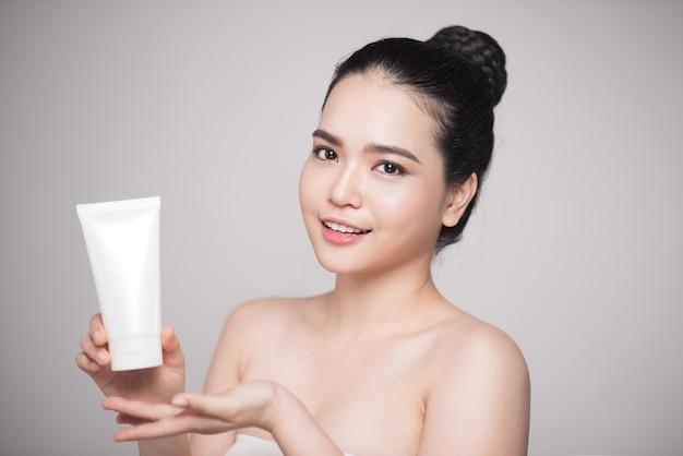 美容コンセプト。化粧品ボトルを保持している完璧な肌を持つアジアのきれいな女性