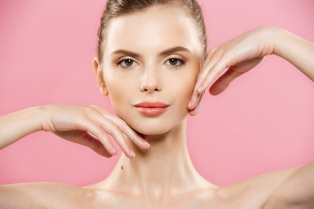 Beauty concept - beautiful caucasian woman with clean skin, natural make-up isolated on bright pink background with copy space.