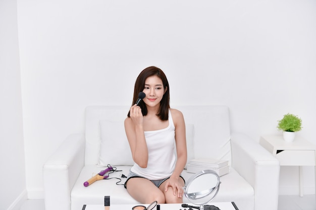 Beauty concept. beautiful girl doing makeup at home