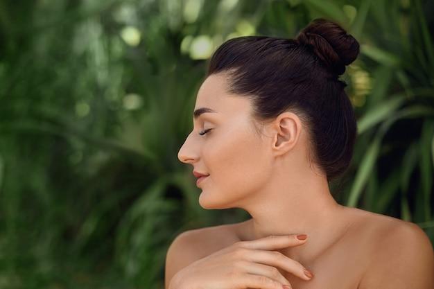 뷰티 개념. 완벽 한 깨끗한 피부와 아름 다운 여자 모델입니다. 열 대 잎에 여자의 초상화입니다. 몸과 피부 관리.
