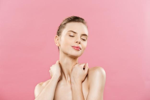Концепция красоты - красивая женщина с чистой свежей кожей закрыть на розовой студии. уход за кожей лица. косметология.