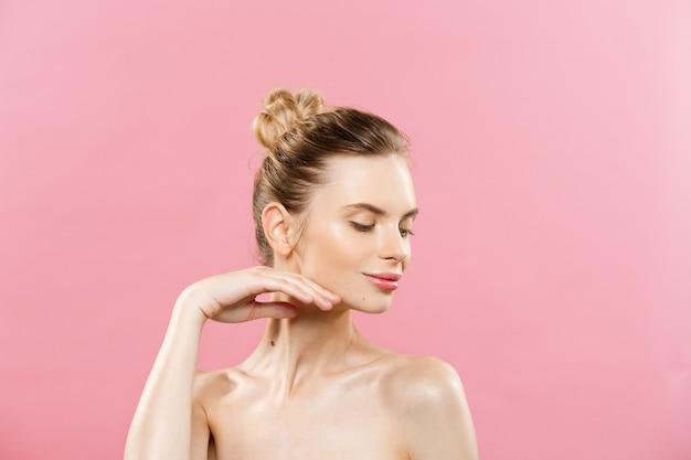 美容の概念 - きれいな新鮮な皮膚を持つ美しい女性は、ピンクのスタジオに閉じます。スキンケアの顔。化粧品。