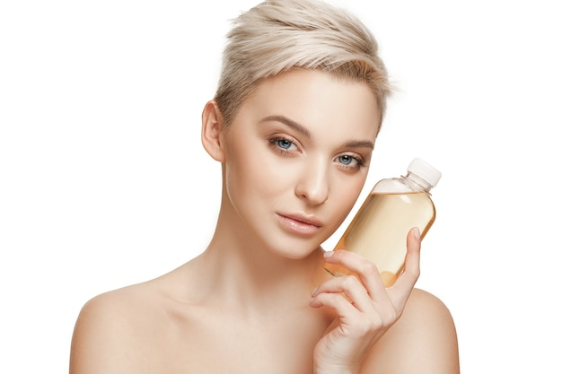 美容コンセプト。オイルボトルを保持している完璧な肌を持つ白人のきれいな女性