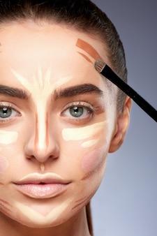 美容コンセプト。メイクアップをしている、顔に輪郭を描く女性のクローズアップの肖像画。メイクの種類、カメラを見ている女性、ブラシで顔に線を描く