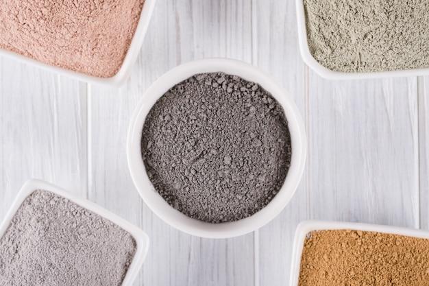 뷰티 개념. 평평한 누워, 다른 점토 진흙은 집에서 만든 페이셜 및 바디 마스크 또는 스크럽을위한 천연 성분을 가루로 만듭니다.
