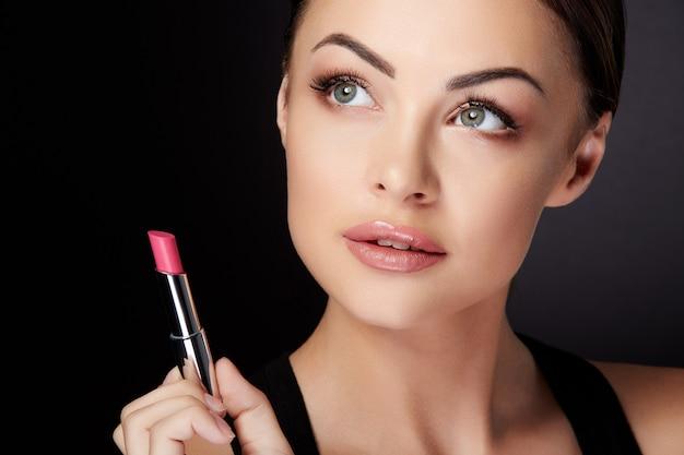美しさの概念、バラの口紅を持って、見上げて脇に女性の頭と肩。リップグロスで描かれたバラの唇を持つモデルの美しさの肖像画、黒い背景のスタジオ