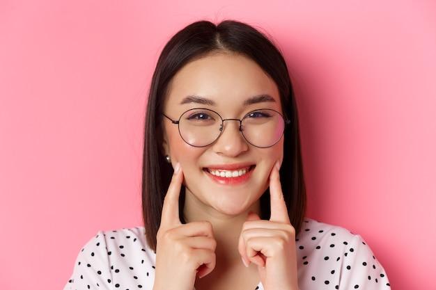 뷰티 개념. 웃고, 뺨을 파고, 분홍색 위에 서있는 귀여운 보조개를 보여주는 유행 안경에 사랑스러운 아시아 여자의 얼굴 만.