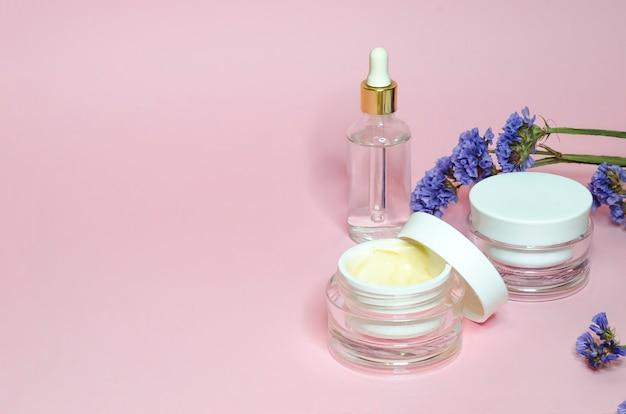 Концепция красоты. натуральная косметика для ежедневного ухода за кожей в стеклянной банке на розовом фоне. продукт крем и сыворотка против морщин, омолаживающий, лифтинг, освежающий, очищающий, увлажняющий эффект.