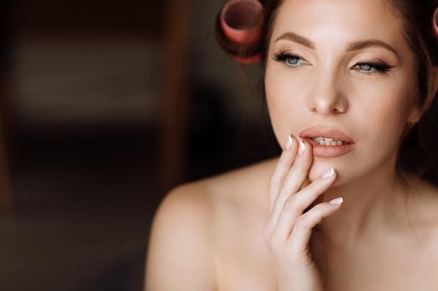 Концепция красоты. портрет красивой молодой эффектной брюнетки с ярким макияжем в стиле пин ап в розовых бигуди.