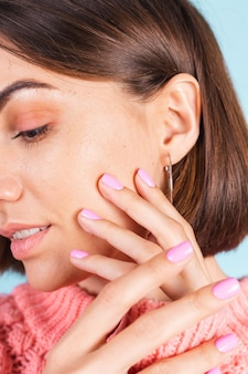 Beauty concept, pretty woman with bright pink nail color manicure on wall