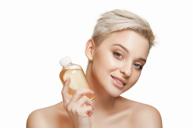 Beauty concept the pretty woman with perfect skin holding oil bottle