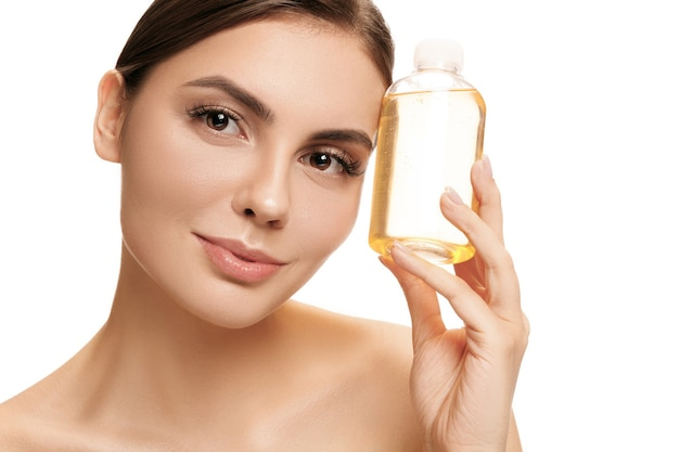 美容コンセプト。スタジオでオイルボトルを保持している完璧な肌を持つ白人のきれいな女性。美容、ケア、肌、トリートメント、健康、スパ、化粧品、広告のコンセプト