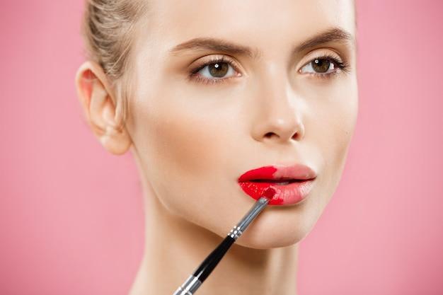 美容の概念 - ピンクのスタジオの背景と赤い口紅を適用している女性。美しい女の子が化粧をする。