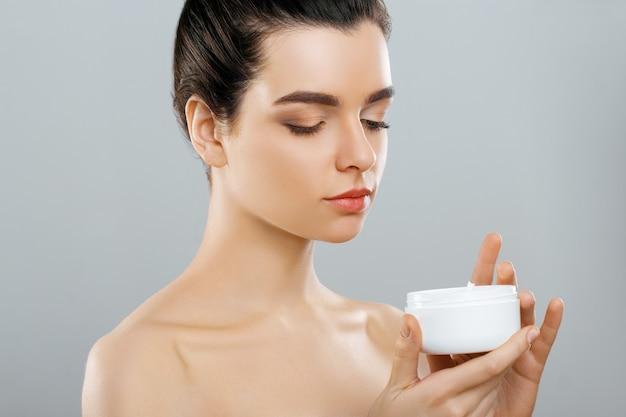 美容コンセプト。女性は保湿クリームを持っています。ボディケア、スキンケア。お肌のケア