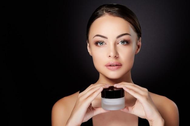 Концепция красоты, женщина смотрит в камеру и держит крем в руках перед ней. голова и плечи молодой женщины с гладкой кожей, уход за собой. студия, черный фон