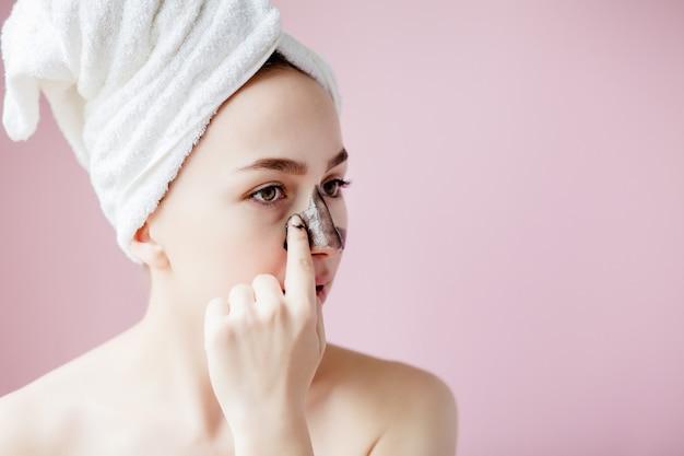 美容化粧品の剥離。クローズアップ黒の美しい若い女性が肌のマスクをはがします。顔に化粧品スキンケア剥離製品と魅力的な女性のクローズアップ。 Premium写真