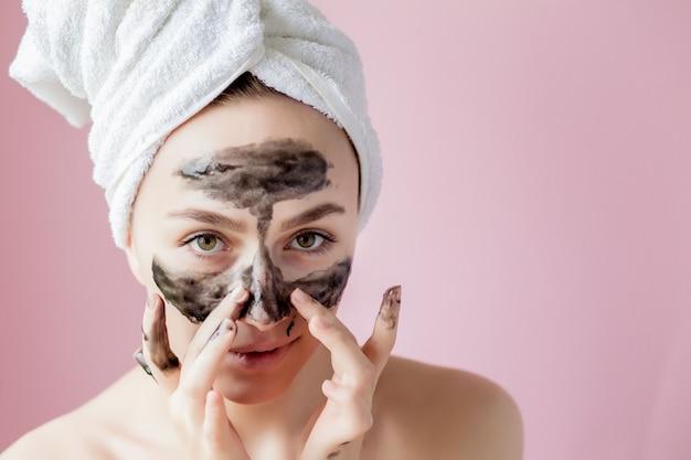 美容化粧品の剥離。クローズアップ黒の美しい若い女性が肌にマスクをはがす