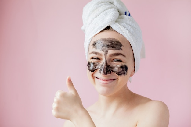 Beauty cosmetic peeling. closeup beautiful young female with black peel off mask on skin