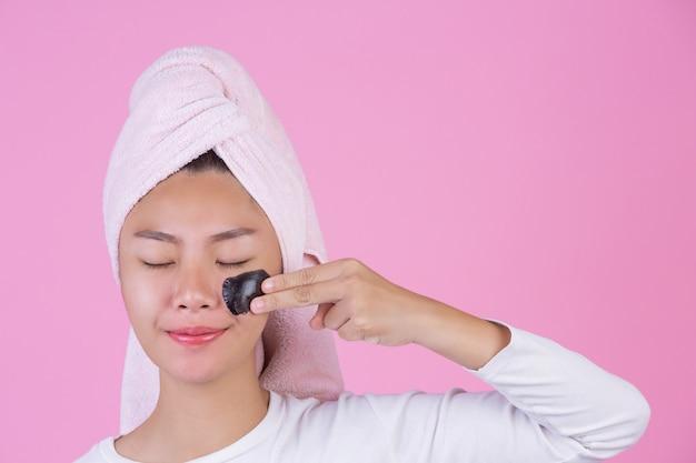 美容化粧品の剥離。黒の若い女性は、ピンクの顔に皮膚化粧品スキンケア剥離製品のマスクをはがします。 無料写真