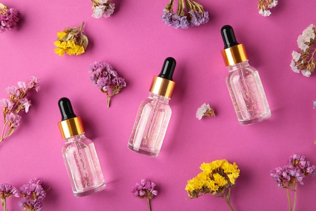 Beauty cosmetic skincare oil in bottle. products with flower on purple background. top view. copy space for text