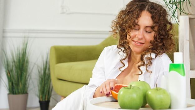 Концепция косметики красоты. красивая молодая женщина с вьющимися волосами и здоровой кожей в комнате с зеленым диваном. яблоки и органический уход на деревянном столе