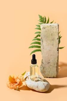 Косметическое масло или экстракция в стеклянной бутылке на каменном подиуме, украшенном живыми цветами и растительным папоротником на бежевом пространстве