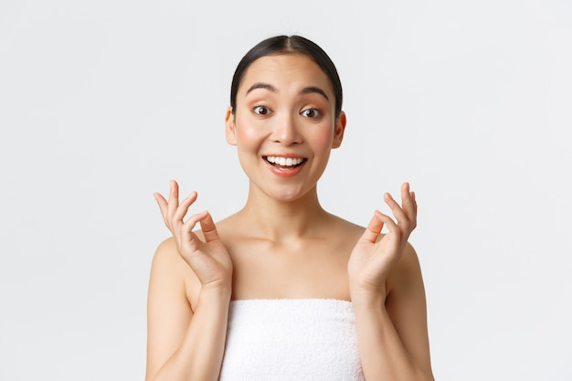 Beauty, cosmetology and spa salon concept. surprised and happy beautiful asian girl in towel react to clean perfect skin after skincare or massage therapy, look impressed and satisfied.
