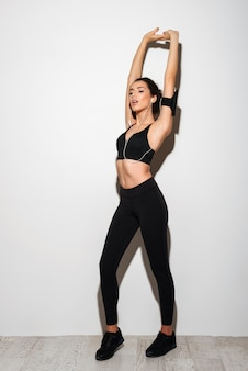 Beauty curly brunette fitness woman stretching