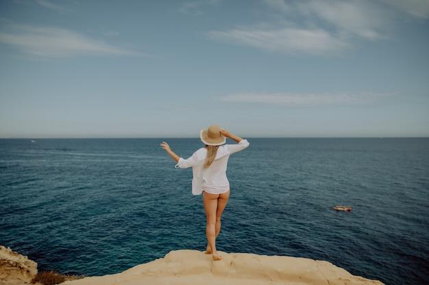 Девушка красоты милая на берегу океана моря тропического пляжа с большими камнями.