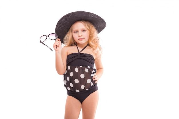 Beauty cute little girl in in black swimwear and black hat hold glasses