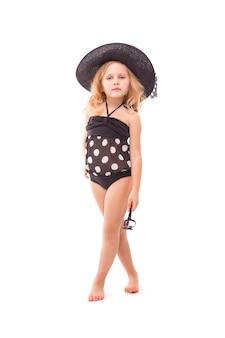 Красота милая маленькая девочка в черном купальнике и черной шляпе держать очки