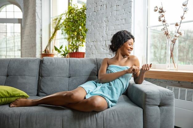 美容の日。自宅で毎日のスキンケアルーチンを行うために準備されたタオルを着たアフリカ系アメリカ人の女性。ソファに座って、マニキュアをして、笑っています。美容、セルフケア、化粧品、若さ、健康の概念。
