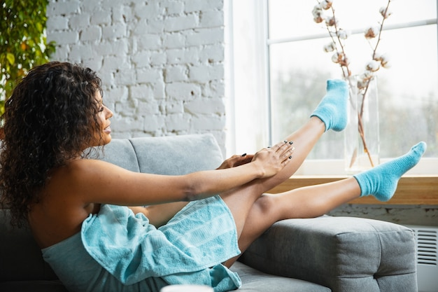 Beauty day. african-american woman in towel doing her daily skincare routine at home. sitting on sofa, massaging putting on moisturizer on leg's skin. concept of beauty, self-care, cosmetics, youth.