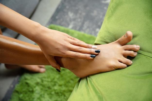 美容の日。自宅で毎日のスキンケアルーチンをしているタオルを着ている女性のクローズアップ。ソファに座り、保湿剤をつけ、足の皮膚をマッサージします。